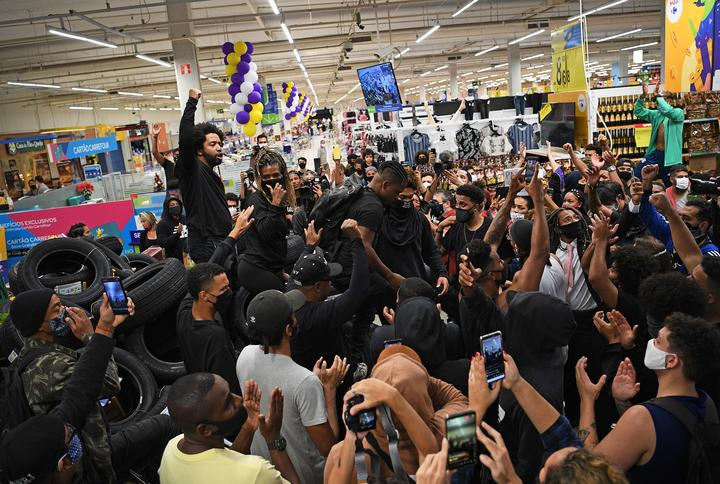 Demonstrators make a barrier out of car tyres inside the supermarket Carrefour in Rio de Janeiro, Brazil.