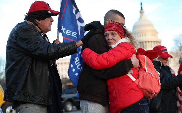Gary Phaneuf, Tony Naples and Melody Black share a moment together as they visit a memorial setup near the U.S. Capitol Building for Ashli Babbitt who was killed in the building after a pro-Trump mob broke in on January 07, 2021 in Washington, DC.