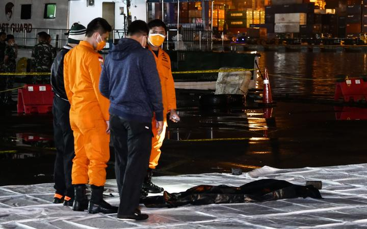 Officers from Sriwijaya Air and The National Search and Rescue Agency of Indonesia ) check a fragment of Indonesian Sriwijaya Air Flight 182 Boeing 737 crashed into the Java Sea on Saturday (9/1) at a Port in Jakarta, Indonesia on January 10, 2021.