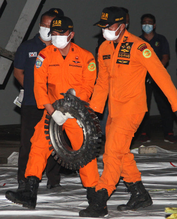 Rescue personnel carry a piece of wreckage recovered from the crash site of Sriwijaya Air flight SJ182 at the port in Jakarta on January 10, 2021, following the January 9 crash of the airline's Boeing 737-500 aircraft into the Java Sea minutes after takeoff.