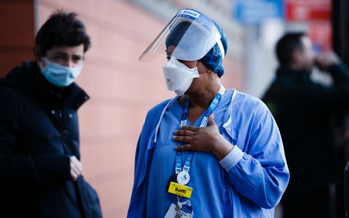 A medic wearing a face mask and visor stands outside the emergency department of the Royal London Hospital in London, England, on January 9, 2021.