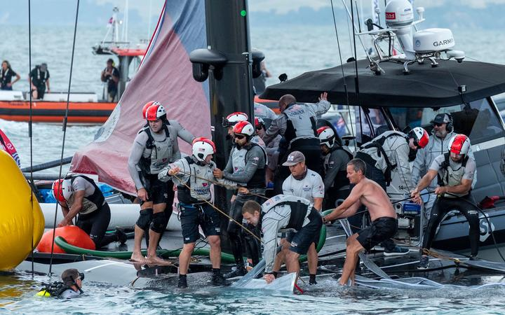 Emirates Team New Zealand sailor Richard Meacham (shirtless) assists with the recovery of Patriot after American Magic capsize in their Round Robin 2 match against Luna Rossa Prada Pirelli Team. Prada Cup. Sunday 17th of January 2021.
