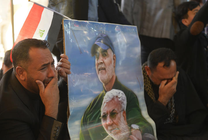 Iraqis holding portraits of slain commander Abu Mahdi al-Muhandis (bottom) and Iranian Revolutionary Guards commander Qasem Soleimani, during a ceremony on January 3, marking the first anniversary of their killing in a US drone strike.