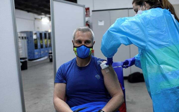 A health worker administers the Pfizer-BioNTech COVID-19 vaccine to a member of the Emergency Medical Services of Madrid (SUMMA) in Madrid on January 12, 2021.