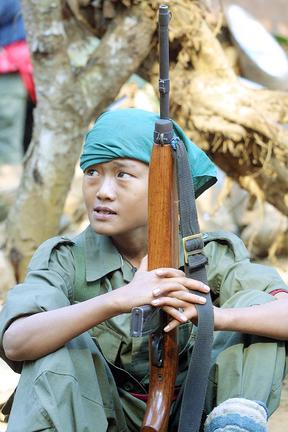 Karen National Union children soldier holds a gun  during the anniversary of the 53rd Karen National Resistance Day at Valay Kee base near Thailand-Myanmar border 31 January 2002. Karen are the largest ethnic minority in Myanmar and have been fighting for independence more than 50 years.