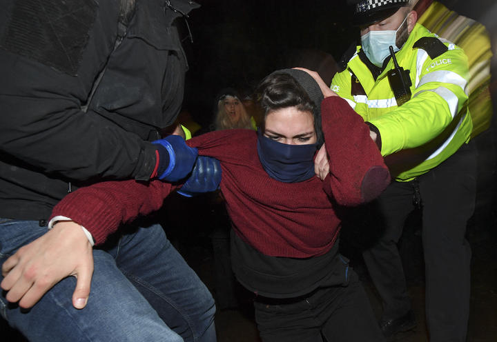 Police officers scuffle with people gathering at a band-stand where a planned vigil in honour of murder victim Sarah Everard was cancelled after police outlawed it due to Covid-19 restrictions.
