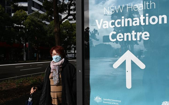 A woman walks past the vaccination centre signage in Sydney on June 29, 2021, as about 10 million Australians have been ordered into lockdown as Covid-19 spreads across the country