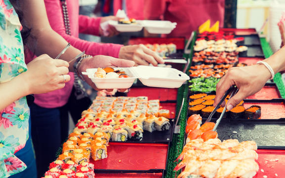 cooking, asian kitchen, sale and food concept - close up of hands with tongs taking sushi at street market