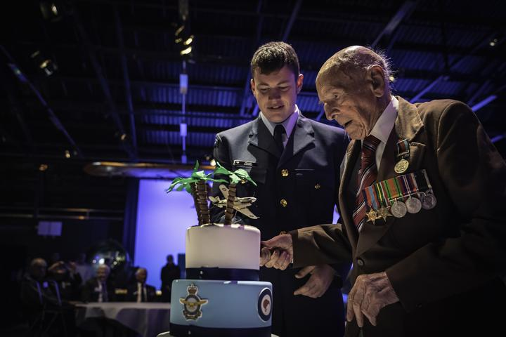 Ron Hermanns cutting his 108th birthday cake with help from the youngest serving airman in the RNZAF at the time, Aircraftman Hamish Batchelor (then 18).