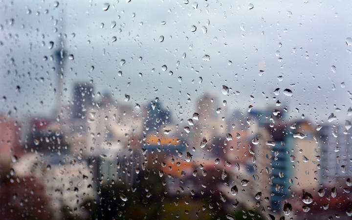 Urban view of rain drops falls on a window during a stormy day overlooking Auckland CBD New Zealand skyline in the background.