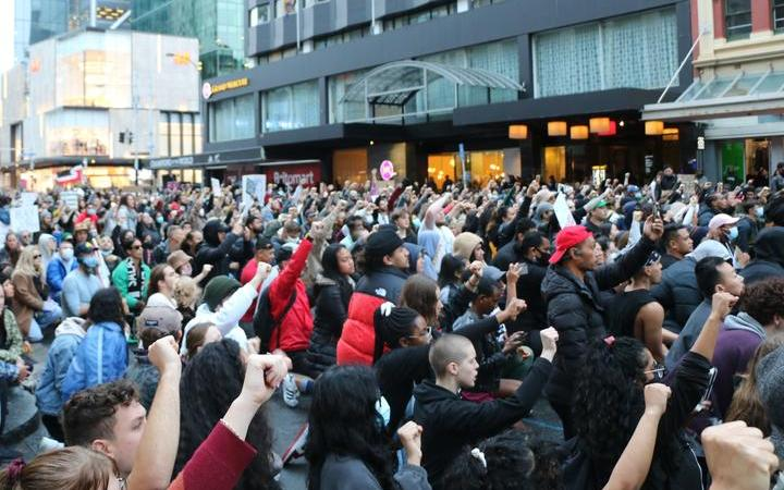 """Protesters took a knee with fists up outside the US embassy building in Auckland on 1 June, 2020, chanting """"Black lives matter""""."""
