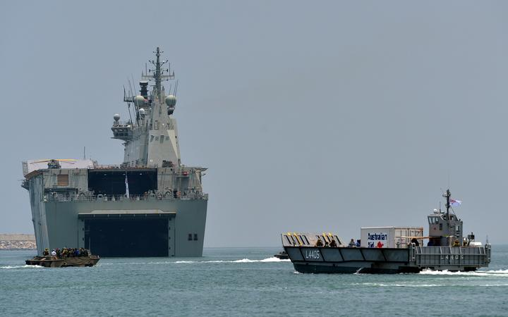 The Royal Australian Navy ship HMAS Canberra (L02) (C) and landing craft (R) take part in training excercise in the Sri Lankan capital Colombo on March 26, 2019.