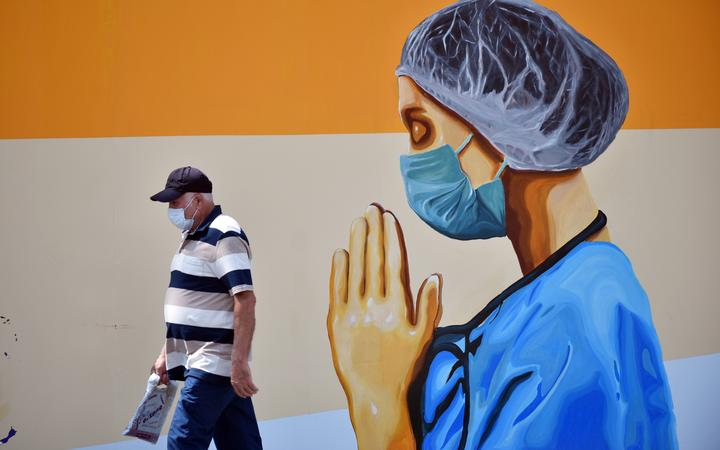 A man wearing face mask walks past a mural depicting of a healthcare worker and a world map with flags on walls of idle cinema building in Mersin, Turkey on June 23, 2020.