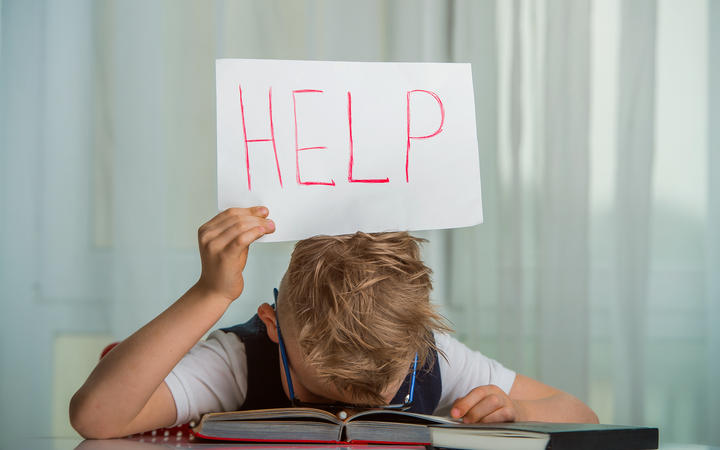 Kid boy sleeping with a textbook over his head and holding a sign with the word Help