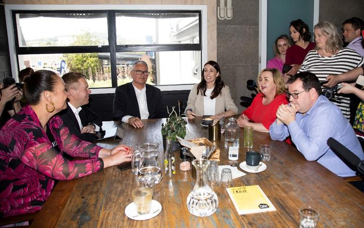 New Zealand Prime Minister Jacinda Ardern (centre R) speaks with senior members of parliament a day after her landslide election win.