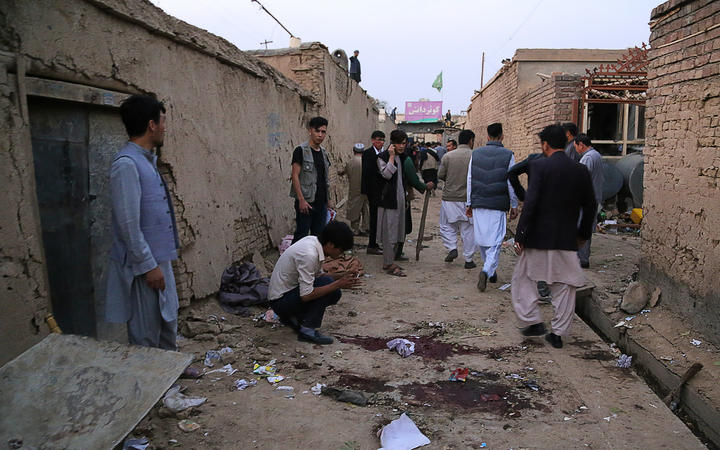 Residents gather near the site following the suicide bombing.