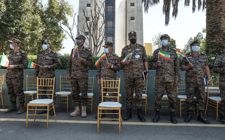 Members of the Ethiopian Army stand holding Ethiopian national flags during an event to honour the national defence forces in Addis Ababa, on November 17, 2020.