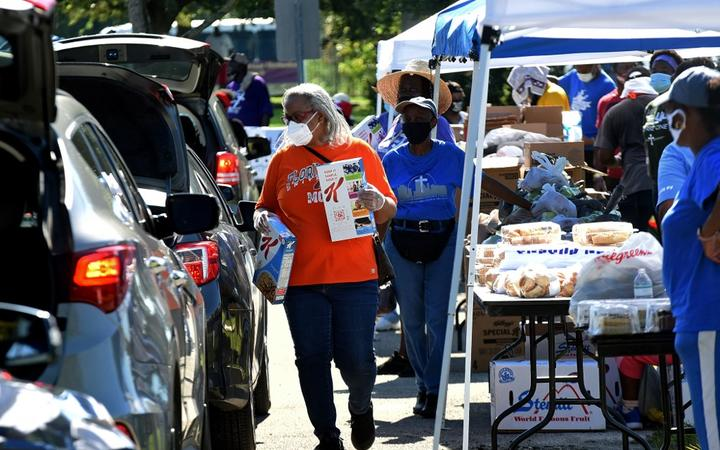 Volunteers distribute food from the Second Harvest Food Bank of Central Florida at Carter Tabernacle Christian Methodist Episcopal Church on August 8, 2020 in Orlando, Florida.