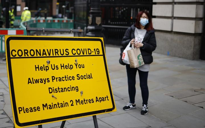 A shopper wearing a facemask stands near a sign promoting social distancing in Haymarket, central London on January 8, 2021, as England entered a third lockdown due to the novel coronavirus Covid-19.