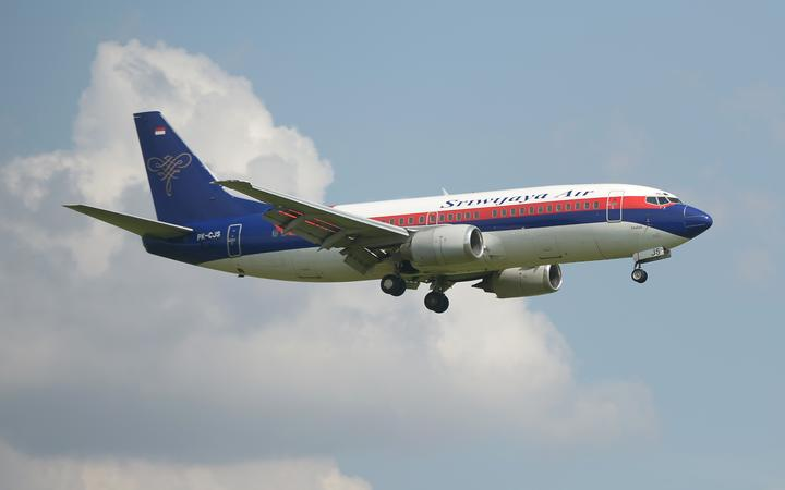 This picture taken in Tangerang on March 18, 2013 shows an Indonesian Sriwijaya air plane preparing for landing over the Sukarno-Hatta airport in Tangerang.