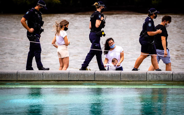 Police patrol past mask-clad people on the deserted South Bank beach on the first day of a snap lockdown in Brisbane on January 9, 2021