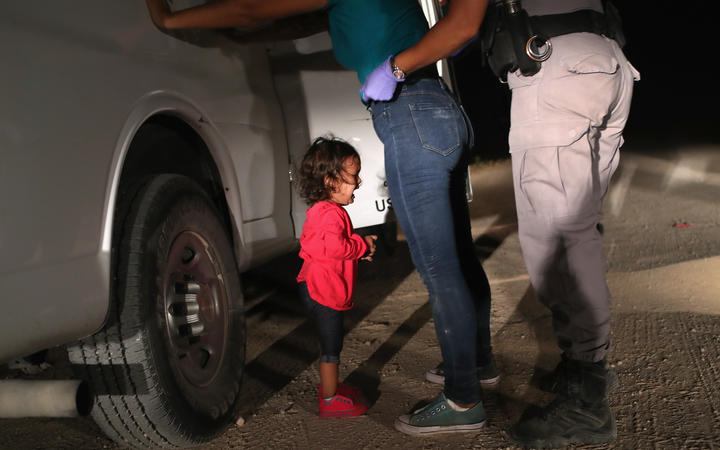 (FILES) In this file photo taken on June 11, 2018 a two-year-old Honduran asylum seeker cries as her mother is searched and detained near the U.S.-Mexico border in McAllen, Texas.