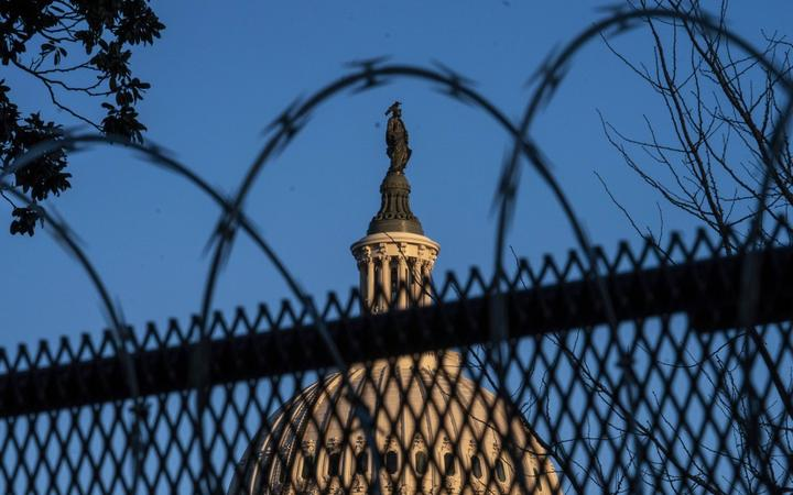 The exterior of the U.S. Capitol building is seen through barbed wire fencing at sunrise on February 8, 2021 in Washington, DC.
