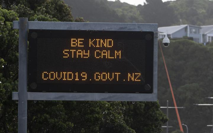 """A motorway sign reads """"Be kind and stay calm"""" along a street devoid of cars in response to the COVID-19 coronavirus outbreak in Wellington on April 20, 2020."""