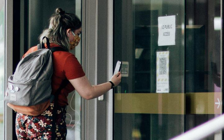 A woman using the Covid Tracer app at a QR code in the window of a business during level 2 in Wellington on15 February 2021