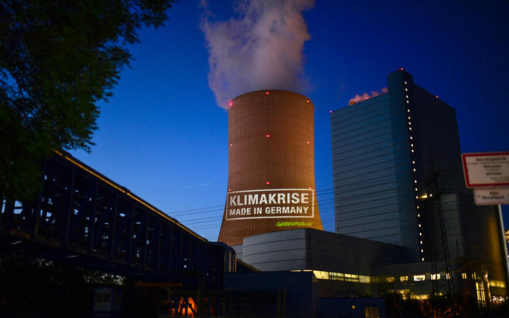 """Greenpeace activists project the slogan """"Climate crisis  made in Germany"""" on the coal-fired power plant Datteln 4 of Uniper in Datteln, Germany, on May 30, 2020."""
