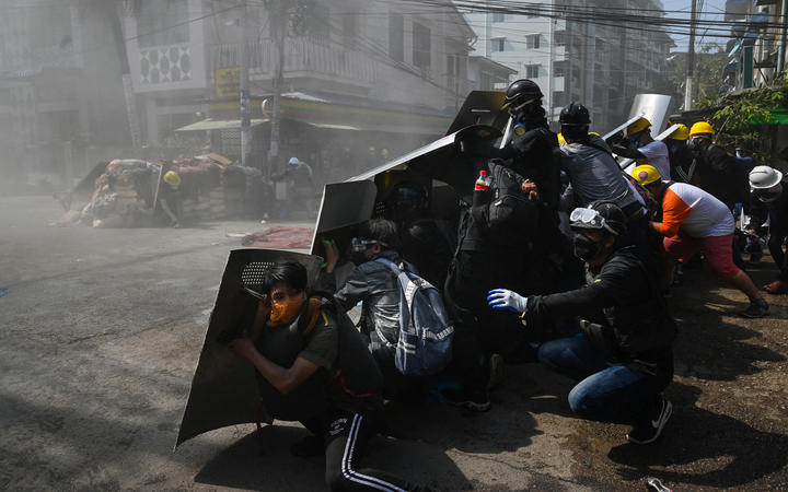 Protesters take shelter behind homemade shields after tear gas was fired during a demonstration against the military coup in Yangon.