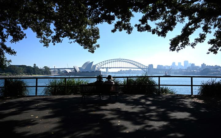 A couple enjoy the view of Sydney Harbour from Mrs Macquarie's Chair on May 3, 2021, as Australia's largest city is enveloped in a thick bank of hazardous bushfire smoke forcing authorities to scale back controlled forest burning nearby.