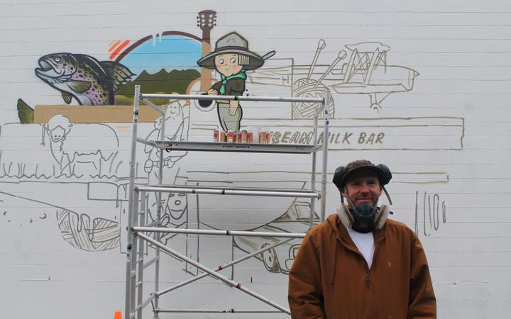 Before...artist Sean  Duffell starts to fill in the  outline of his Streets  Alive street art mural last   Wednesday.