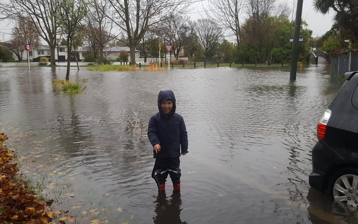 Four-year-old Finn Thorp checking out water levels at the corner of Clarendon Terrace and Sheldon Street, next to the Heathcote River.