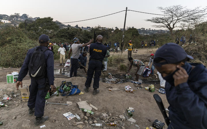 Police officers argue with members of the community next to a looted  warehouse storing alcohol in Durban on July 16, 2021,