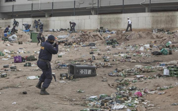 A member of SAPS shoots rubber bullets to disperse a crowd looting outside a warehouse storing alcohol in Durban on July 16, 2021,