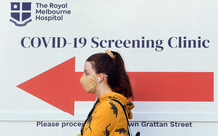 A woman queues outside a Covid-19 coronavirus testing venue at The Royal Melbourne Hospital in Melbourne on July 16, 2020.