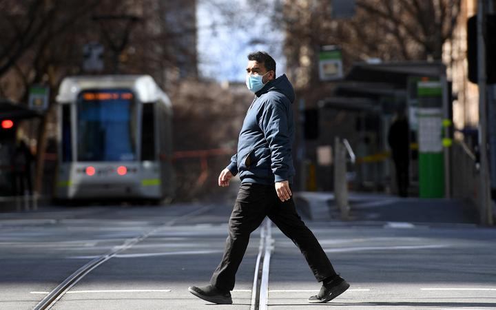 A man crosses an empty street in Melbourne on 23 August 2021, as the city experiences its sixth lockdown while battling an outbreak of the Delta variant of coronavirus.