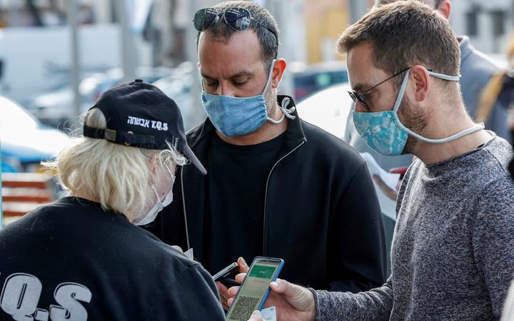 """Attendees present their """"green passes"""" (proof of being fully vaccinated against COVID-19 coronavirus disease) as they arrive at Bloomfield Stadium in the Israeli Mediterranean coastal city of Tel Aviv on March 5, 2021,"""