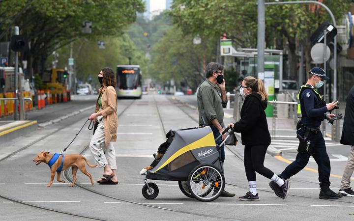 People walk their dogs in Melbourne on 30 September 2021 as the city grapples with a surge in Covid-19 infections.