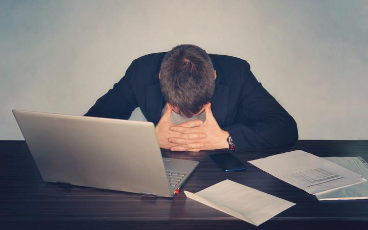 Exhausted tired businessman working on laptop at office, massaging temporal area, holding glasses, feeling fatigue discomfort, eye strain after long wearing spectacles, eyesight problem,