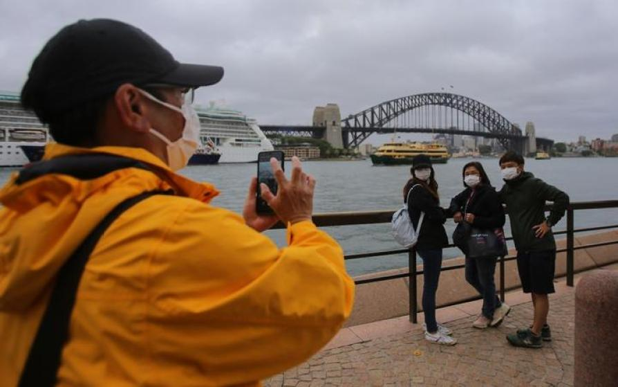 People wear face masks as a preventative measure against Coronavirus COVID-19 in front of the Sydney Harbour Bridge in Sydney, Australia on March 14, 2020.