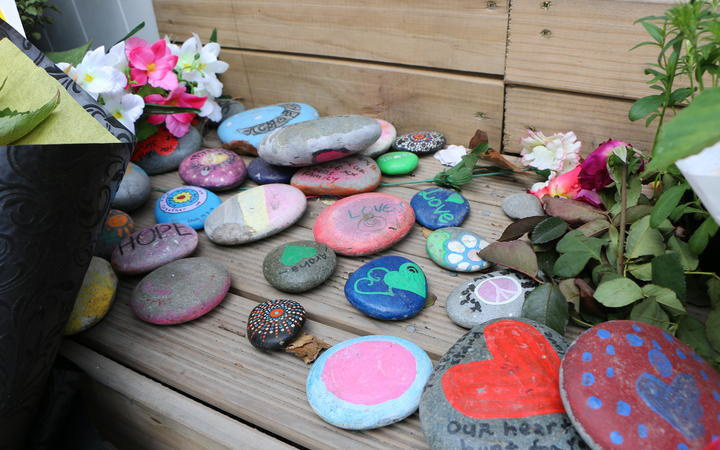 People have left rocks with messages of support and drawings at the Linwood Mosque entrance on the one-year anniversary since the shootings.