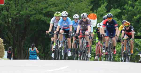 group of cyclists cresting hill