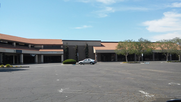 A shopping center sits empty, in anticipation of its demolition for the new freeway.