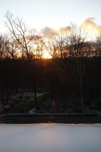Sunset in South Kent with snow on the roof and in the forest