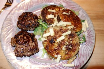 Homemade burgers and breaded eggplant on a bed of arugula