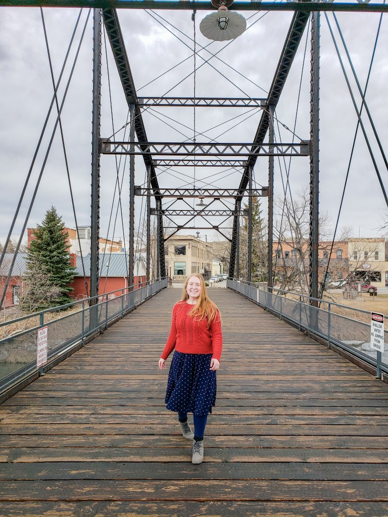 girl in a red sweater and blue skirt stands on a bridge with a wooden floor and iron arches.