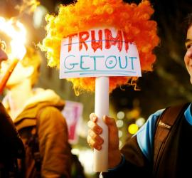 Trump get out, a sign held by young people.