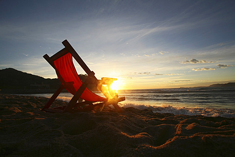 A chair on the sand facing the water, Barra de Navidad, Mexico